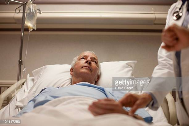 Man in hospital bed having pulse taken