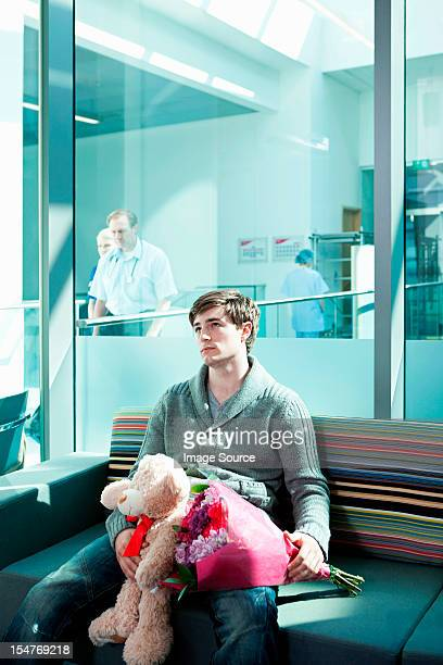 Man in hospital waiting room with bouquet and teddy bear