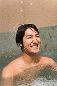 Man in hot tub, smiling, front view, Japan