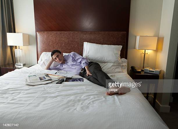 Man in hotel watching tv in bed