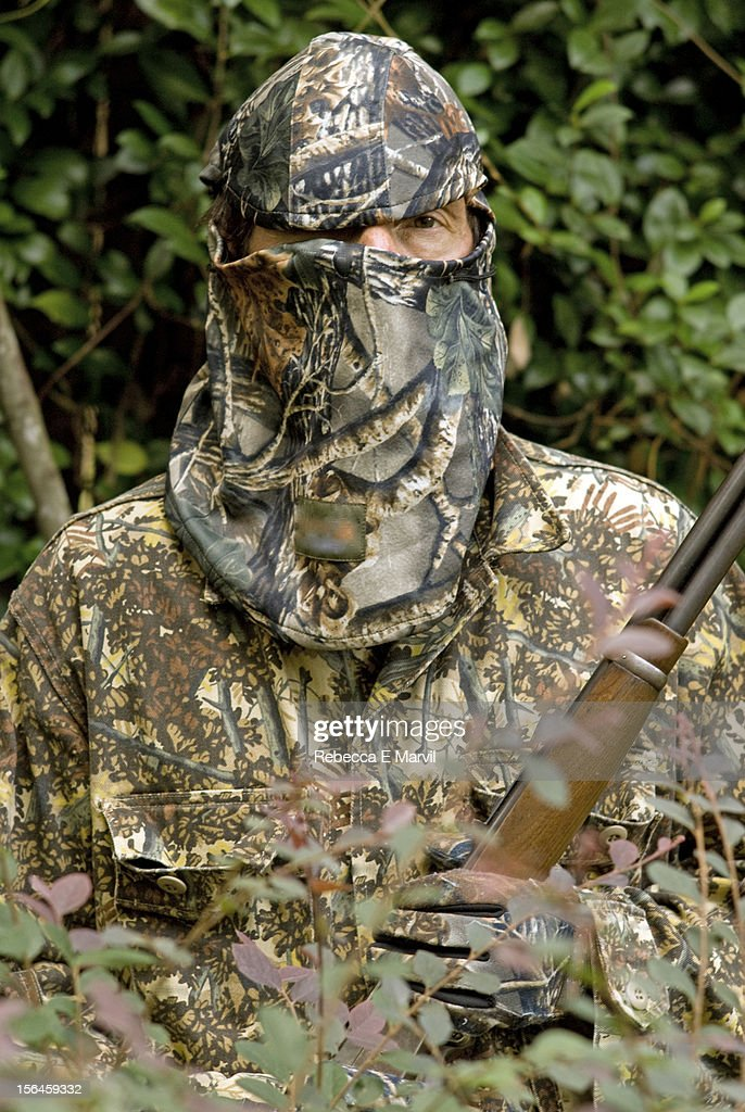 A man in hunting camouflage holding a rifle