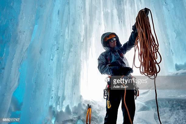 Man in ice cave preparing climbing rope, Saas Fee, Switzerland