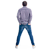 A man in jeans hands in pocket standing on a white background. Isolation, back view