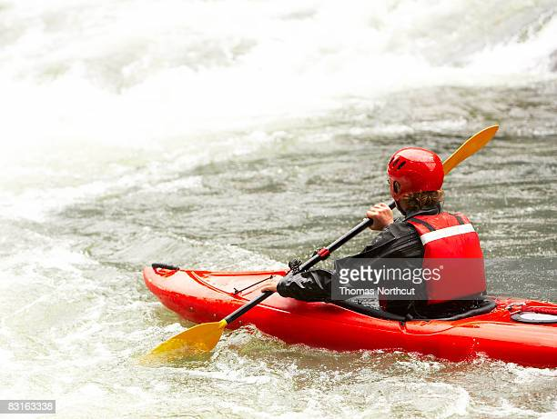 Mann in einem Kajak über, um rapids