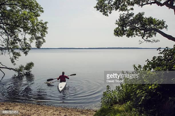 Man in kayak on a lake.