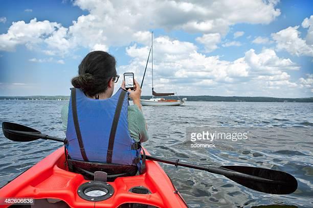 Man In Kayak Taking Photo On Smart Phone