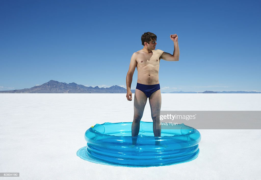 Man in Kiddie Pool in Desert, Flexing Arm : Stock Photo