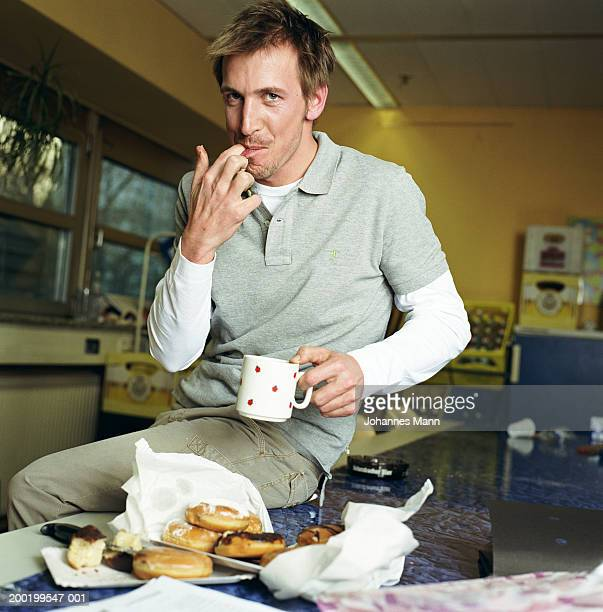Man in kitchen by doughnuts, licking fingers, portrait