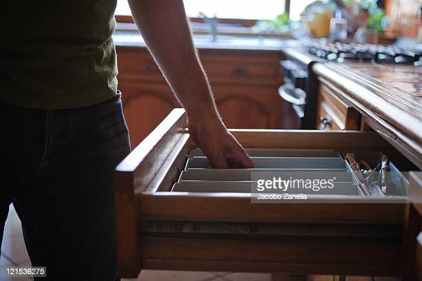 Man in kitchen grabing something from drawer