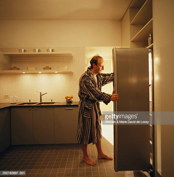 Man in kitchen, holding open fridge door, side view