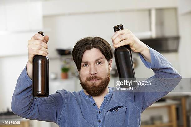 Man in kitchen holding two bottles of beer