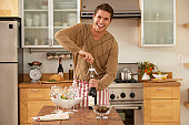 Man in kitchen opening bottle of wine, smiling, portrait