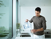 Man in kitchen pouring glass of filtered water
