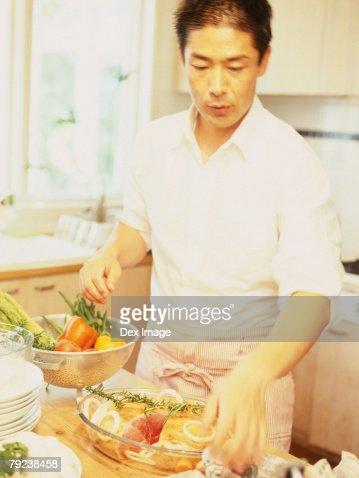 Man in kitchen preparing food : Stock Photo
