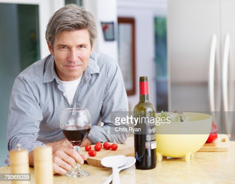 Man in kitchen preparing meal and drinking wine : Stock Photo