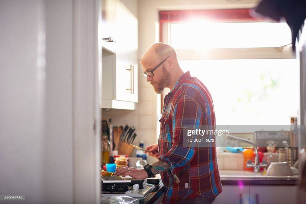 Man in kitchen using laptop whilst making lunch : Stock Photo