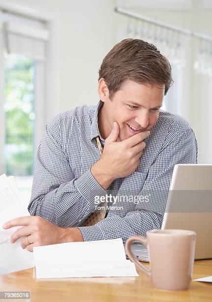 Hombre en cocina con portátil y documentos