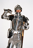 Man in knight's armour costume flexing muscles against white background, portrait