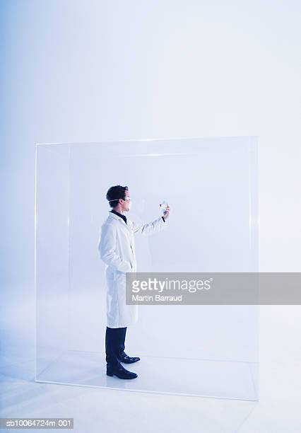 Man in laboratory coat standing in glass cabinet, looking at CD