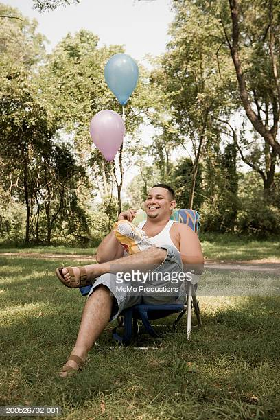 Man in lawn chair eating chips
