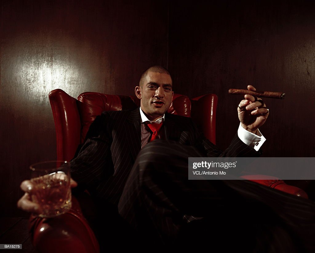 Man in leather chair, holding drink and cigar, portrait : Stock Photo
