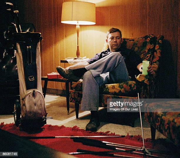 Man in living room by golf clubs