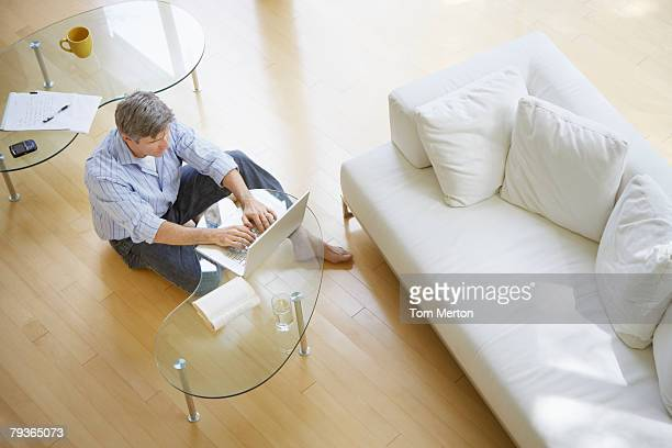 Man in living room sitting on floor using laptop
