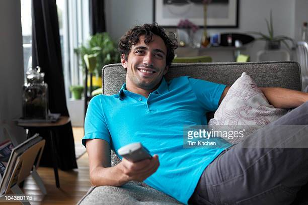 Man in living room with remote control, smiling