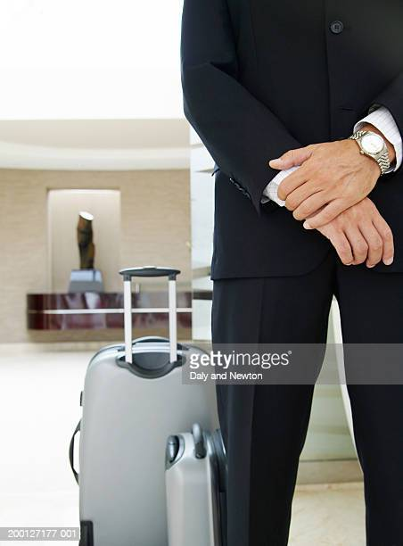 Man in lobby, suitcases at feet, mid section
