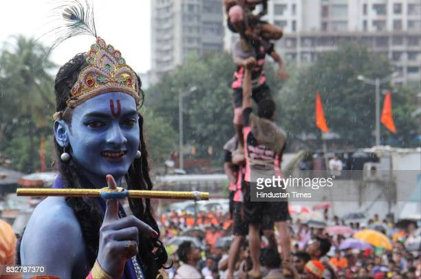 Man in Lord Krishna outfit to form human pyramid to break earthen pots on the occasion of Janmashtami at Borivali on August 15 2017 in Mumbai India...