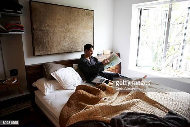 Man in luxury bedroom, bathrobe, morning