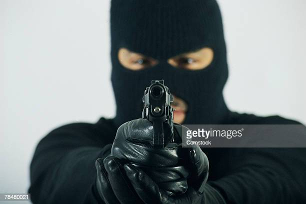 Man in mask aiming gun