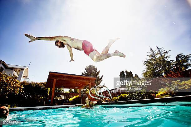 Man in mid air diving into outdoor pool