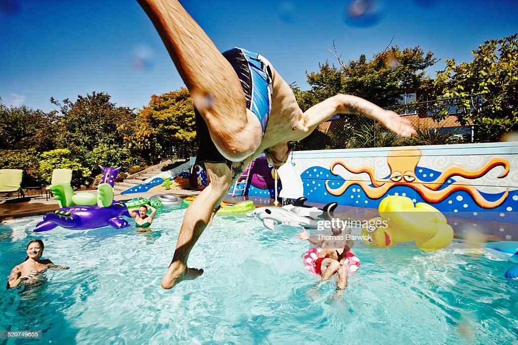 Man in mid air jumping into pool during party : Stock Photo
