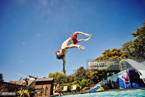 Man in mid air performing backflip into pool
