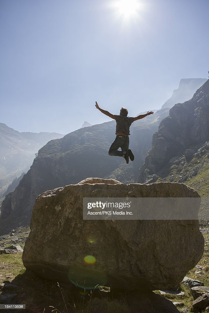 Man in mid-air leap from boulder, in mountains : Stock Photo
