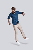 Full length of handsome young man looking down while jumping against grey background