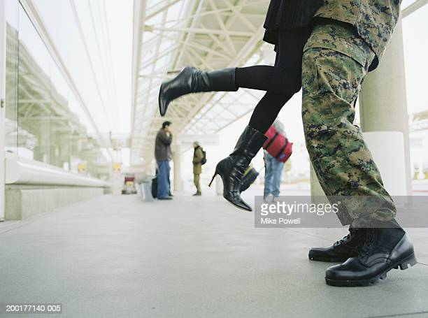 Man in military uniform lifting woman up in airport, low section
