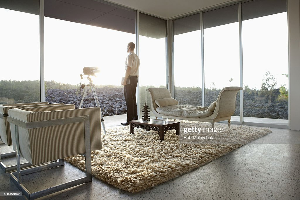 Man in modern room, looking out window to rocks. : Stock Photo