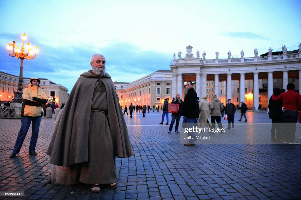 A man in Monks' clothng watches Pope Francis celebrating mass with the cardinals in the Sistine Chapel, as it is shown on a screen in St Peter's square on March 14, 2013 in Vatican City, Vatican. A day after thousands gathered in St Peter's Square to watch the announcement of the first ever Latin American Pontiff it has been announced that Pope Francis inauguration mass will be held on March 19, 2013 in Vatican City.