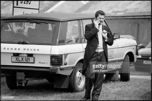 A man in morning dress speaking on a mobile telephone beside a Range Rover on the Epsom Downs on Derby Day 7th June 1997