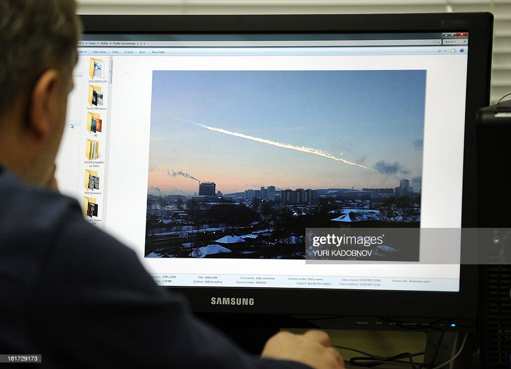 A man in Moscow looks at a computer screen displaying a picture reportedly taken in the Urals city of Chelyabinsk on February 15, 2013, showing the trail of a meteorite above a residential area of the city. A heavy meteor shower rained down today on central Russia, sowing panic as the hurtling space debris smashed windows and injured dozens of stunned locals, officials said. AFP PHOTO / YURI KADOBNOV