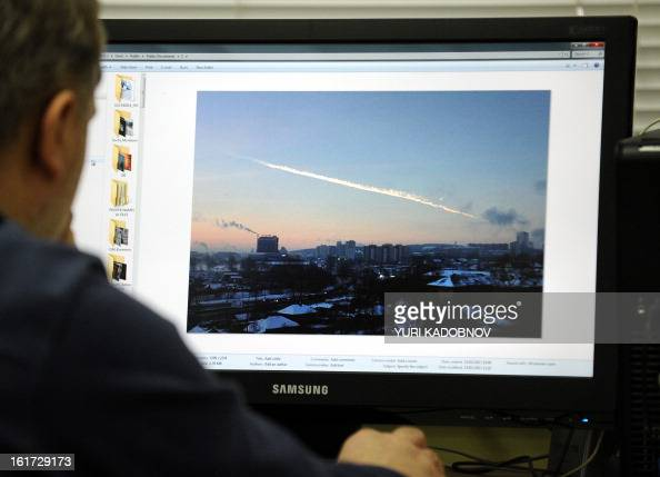 A man in Moscow looks at a computer screen displaying a picture reportedly taken in the Urals city of Chelyabinsk on February 15 showing the trail of...