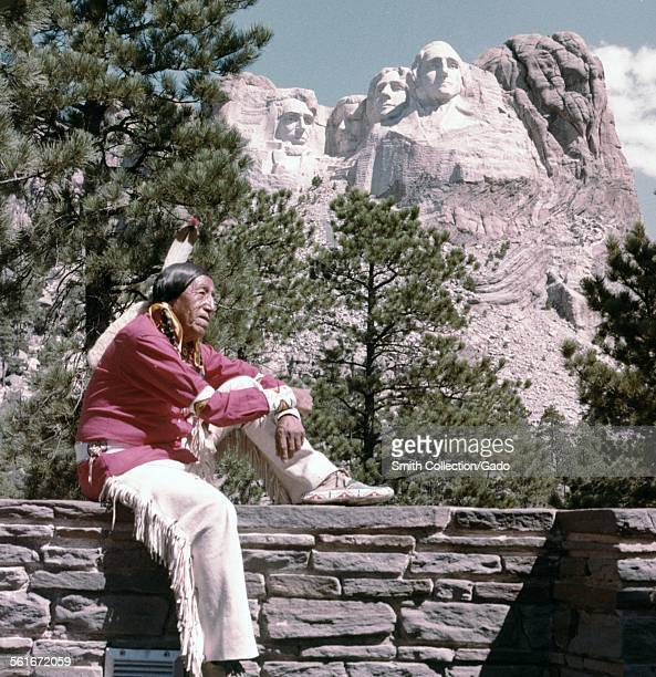 Man in Native American clothing a feather headdress and moccasins sitting on a wall in front of Mount Rushmore National Monument 1962