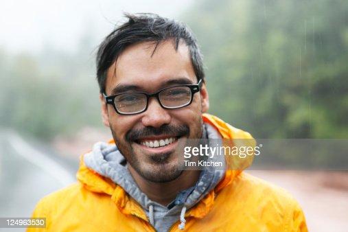 Man in nature during rainstorm, smiling