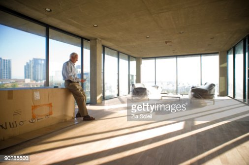 man in new condo checking phone : Stock Photo