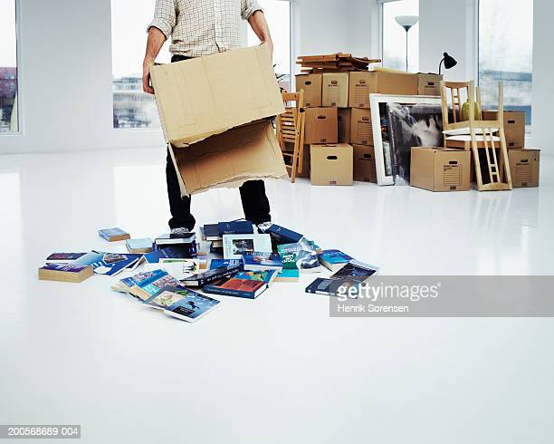 Man in new flat holding cardboard box,books lying on floor,low section