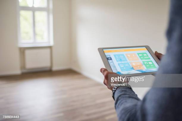 Man in new home using tablet with smart home apps