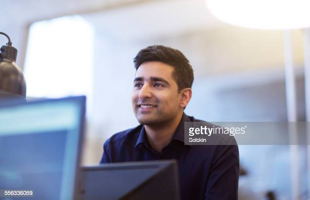 Man in office behind computer screens