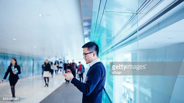 Man in office building text messaging smartphone